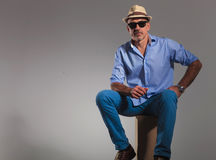 Seated mature man wearing hat and sun glasses Stock Image