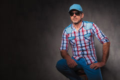 Seated old casual man wearing hat and sunglases Royalty Free Stock Images