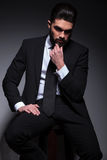 Seated pensive young fashion man looks away Stock Photos