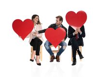 3 seated people holding big red hearts are sharing love stock image