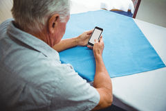 Seated retired man looking at his smartphone Stock Photos