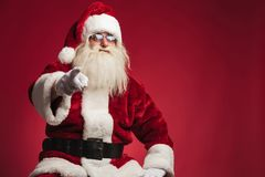 Seated santa claus pointing his finger Royalty Free Stock Photo