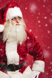 Seated santa looks to side while snowing. On red background Stock Image