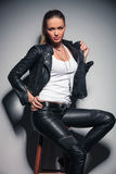 Seated sexy woman in leather clothes. Is holding her coat by collar and one hand on waist Stock Image