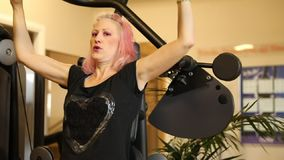 Seated shoulder press machine. Slow motion of smiling female athlete working on seated shoulder press machine. Training arms triceps biceps muscles in modern gym stock footage