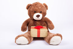 Seated   teddy bear with gift boxes Stock Photos