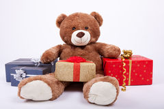 Seated teddy bear with gift boxes Royalty Free Stock Photo