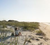 Seated Woman in the Beach Sand Dunes Greets the Rosy New Day royalty free stock image