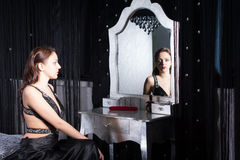 Seated Woman in Black Dress in Front a Mirror Royalty Free Stock Photography