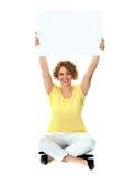 Seated woman holding blank billboard Stock Image