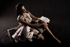 Seated woman with newspapers. Woman seated on floor, her legs covered with newspapers royalty free stock image