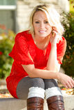 Seated Woman Outside. A young blonde woman sitting outside royalty free stock photos
