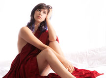 Seated Woman With Red Blanket. A portrait of a pretty woman covered in a red velvet blanket Royalty Free Stock Images