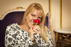 Seated Woman Smiling While Smelling Red Rose Royalty Free Stock Images