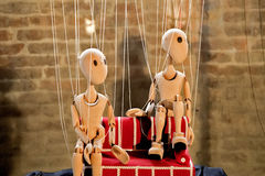 Seated wooden marionettes. Wooden marionettes sit on the red couch Stock Photography