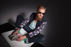 Seated young bearded man looks away Royalty Free Stock Photography