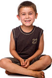 Seated young boy with dirty feet laughing Stock Image