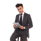 Seated young business man holding tablet Stock Images