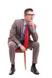 Seated young business man looks away pensively Stock Images