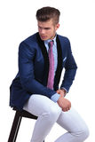 Seated young business man looks to his side Stock Image
