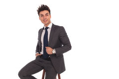 Seated young business man looks up Stock Photography