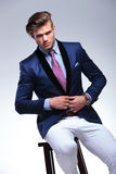 Seated young business man unbuttoning jacket Royalty Free Stock Image