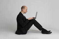 Seated young businessman with laptop Royalty Free Stock Photo