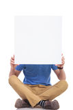 Seated young casual man with blank board Stock Photo