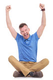 Seated young casual man cheering Stock Images