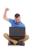 Seated young casual man cheers with laptop Royalty Free Stock Photography