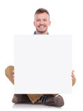 Seated young casual man holds board Stock Photos