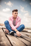 Seated young casual man looking away Royalty Free Stock Photos