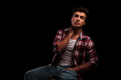 Seated young casual man is looking up. While holding hand behing his neck on black studio background Stock Photography