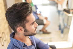 Seated young casual man with nice hairstyle. Side view of a seated young casual man with nice hairstyle, waiting royalty free stock images