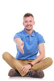 Seated young casual man offers handshake Royalty Free Stock Photo