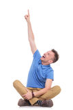 Seated young casual man pointing above him Stock Image