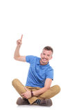 Seated young casual man points upwards. Casual young man sitting on the floor with his legs crossed and pointing up. isolated on white Royalty Free Stock Image