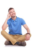 Seated young casual man pondering Royalty Free Stock Images