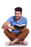 Seated young casual man reading a book and smiles Royalty Free Stock Photo