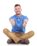 Seated young casual man shows thumbs up Stock Images