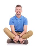 Seated young casual man smiles at camera Royalty Free Stock Images