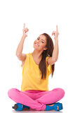 Seated young casual woman pointing up Stock Photos