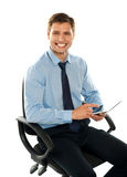 Seated young executive using tablet pc Royalty Free Stock Photography