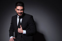 Seated young fashion man smiles and holds jacket Stock Photo