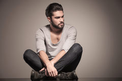Seated young man with beard looks away Stock Images