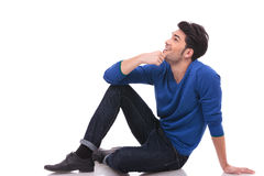 Seated young man in blue jeans and shirt looking up. Side view of a seated young man in blue jeans and shirt looking up at something Royalty Free Stock Photos