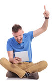 Seated young man cheers with laptop in hand Stock Images