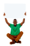 Seated young man holding white blank banner Stock Images
