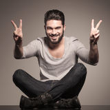 Seated young man making the victory hand sign stock photo