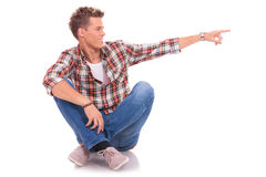 Seated young man pointing to side Royalty Free Stock Photography